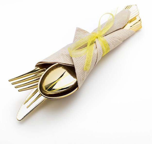 Goldenes besteck (messer, gabel und löffel) mit serviette und schleife. bereit für ein picknick