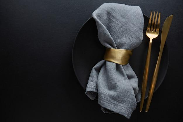 Goldenes besteck mit textil auf teller auf dunklem hintergrund. ansicht von oben.