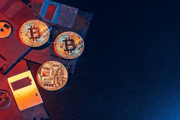 Goldenes bitcoin auf diskette auf dunklem hintergrund