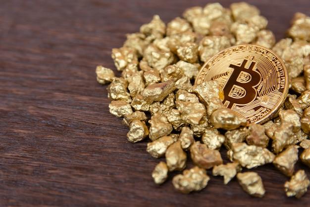 Goldenes bitcoin auf hügel des goldnuggets auf dunklem holz