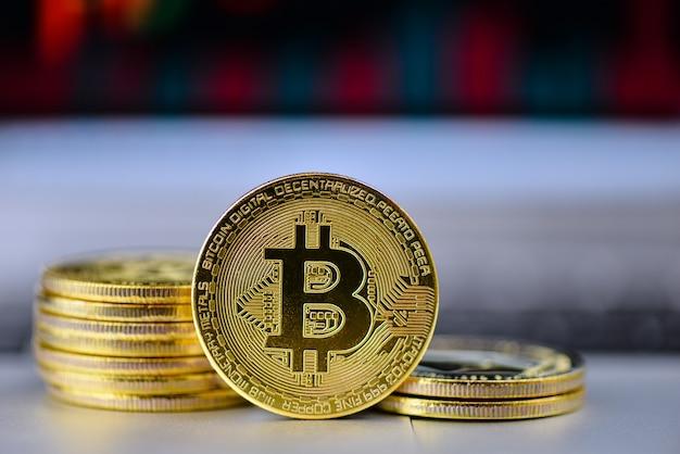 Goldenes bitcoin auf notizbuchtastatur mit diagramm auf hintergrund