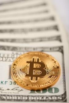 Goldenes bitcoin auf stapel von hundert dollarbanknoten, die zukünftige tendenz des virtuellen geldes darstellen.
