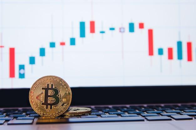 Goldenes bitcoin auf tastaturlaptop mit devisenhandelsdiagramm