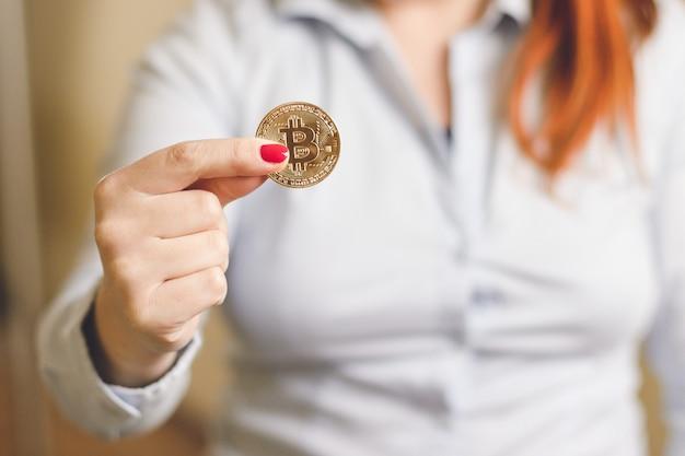 Goldenes bitcoin-konzept der kryptowährung. frau hält eine goldmünze in ihren händen bitcoin
