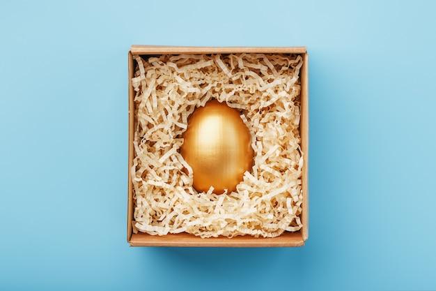 Goldenes ei in einer schachtel auf blauem hintergrund konzept der exklusivität, beste wahl, preis, besondere überraschung, teures geschenk.