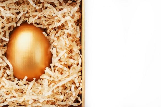 Goldenes ei in einer schachtel auf einem weißen hintergrundkonzept der exklusivität, der besten wahl, des preises, der besonderen überraschung, des teuren geschenks. das konzept des minimalismus.