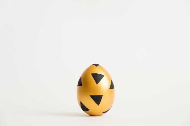 Goldenes ei ostern mit dem geometrischen schwarzen muster lokalisiert auf weißem hintergrund