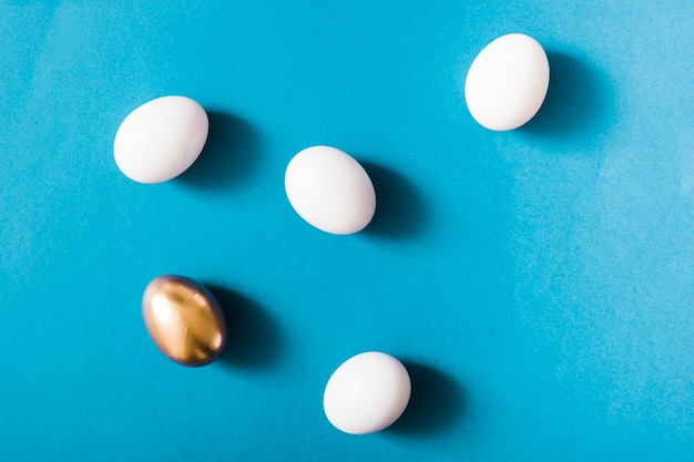 Goldenes ei und weiße eier auf blauem hintergrund