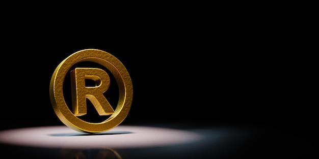Goldenes eingetragenes warenzeichensymbol angestrahlt auf schwarzem hintergrund