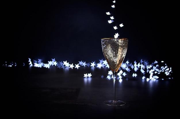 Goldenes festliches glas auf dunklem hintergrund und magisches bokeh in form von sternen, die in das glas strömen. weihnachtshintergrund, platz für text.