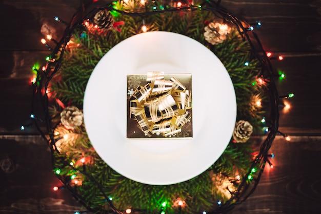 Goldenes geschenk auf der platte im kranz
