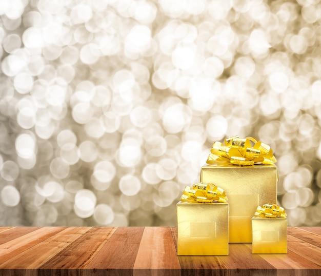 Goldenes geschenk auf holztischplatte mit verschwommenem funkelndem goldbokehhellhintergrund