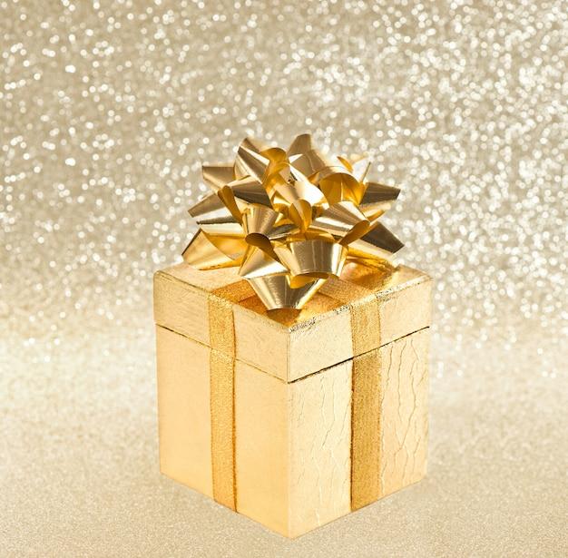 Goldenes geschenk mit farbband über glänzendem hintergrund