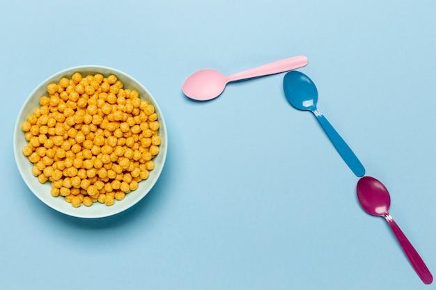 Goldenes getreide in der blauen schüssel mit löffelebenenlage