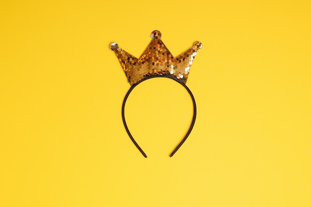 Goldenes glitzerkronenstirnband auf gelbem hintergrund.