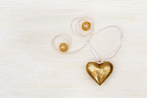 Goldenes herz mit band und perlen