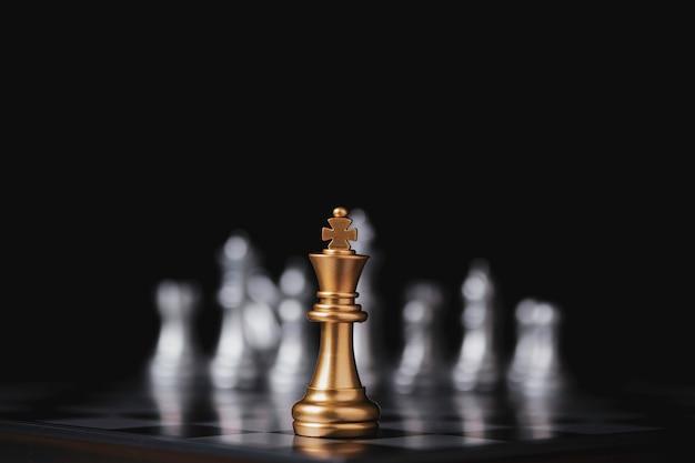 Goldenes königschach vor silbernem bauernschach auf schachbrett und schwarzem hintergrund.