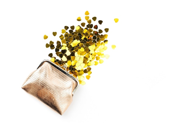 Goldenes konfetti fällt aus der handtasche auf weißem hintergrund
