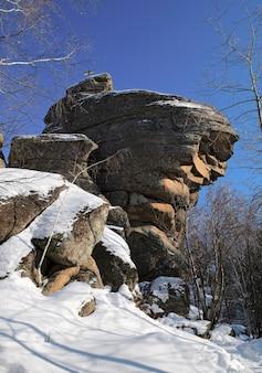 Goldenes kreuz auf einem riesigen steinfelsen mit schnee bedeckt naturskulptur auf dem berg tserkovka