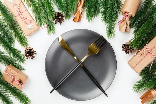 Goldenes messer und gabel gekreuzt auf schwarzem teller auf dem weihnachtstisch mit rahmen aus tannenzweigen mit ...