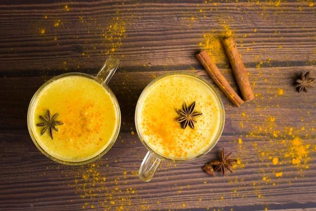 Goldenes milchgetränk mit kurkuma und honig auf dunklem holz