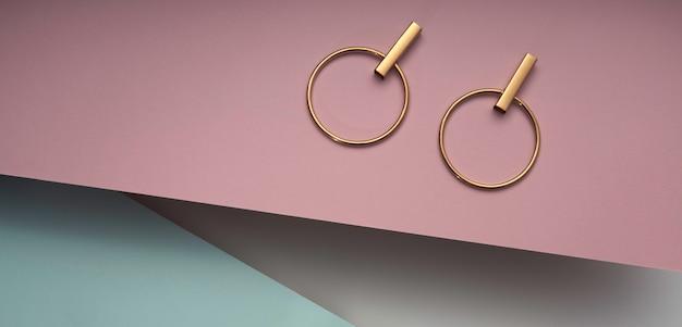 Goldenes modernes ohrringpaar auf rosa und blauem hintergrund. kreisen sie die goldenen ohrringe des modernen designs auf pastellfarbenhintergrund ein