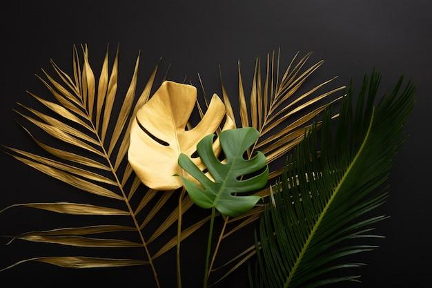 Goldenes palmblatt und grüne frische tropische monstera hinterlassen textur auf dunkelschwarzem hintergrund. gemalte goldblätter und grüne tropische pflanzen auf sommerblumenhintergrund.