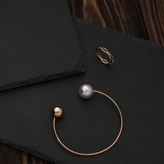 Goldenes perlenarmband und goldener ring auf schwarzer steinplatte auf holztisch