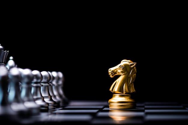 Goldenes pferd schach trifft auf silbernen schachfeind auf schachbrett und schwarzem hintergrund.