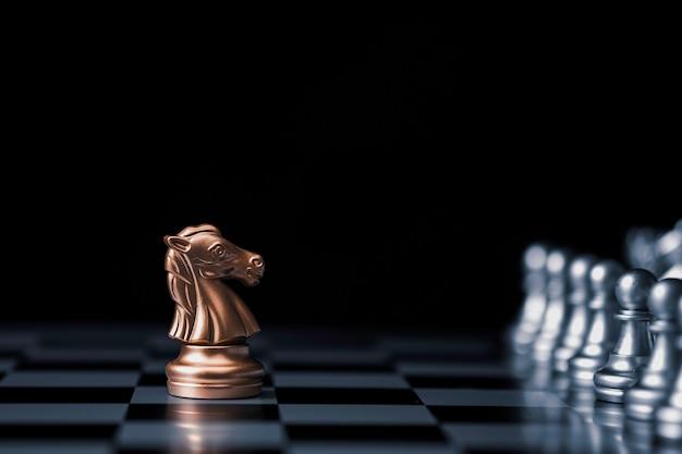 Goldenes pferd schach trifft auf silbernen schachfeind auf schachbrett
