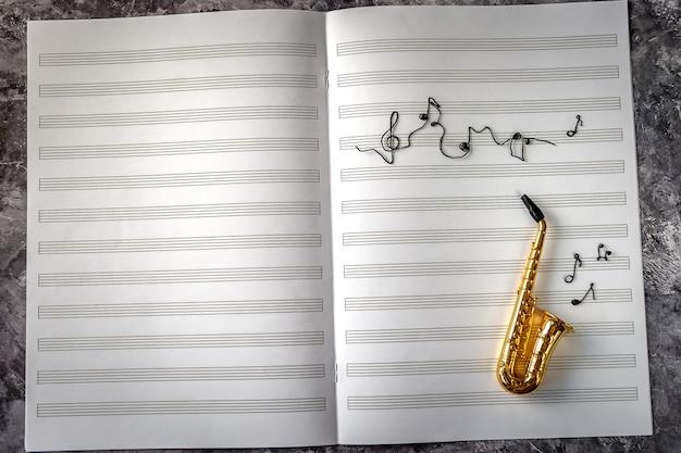 Goldenes saxophon auf hintergrund des musiknotizbuchs mit den noten