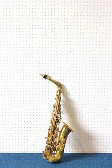 Goldenes saxophon auf weißem und blauem wandhintergrund