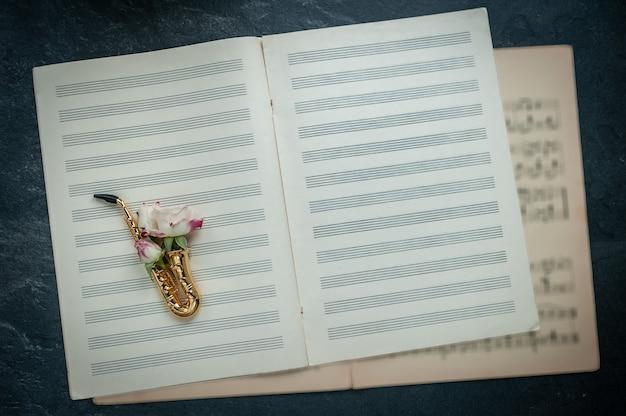 Goldenes saxophon mit rose auf hintergrund des musiknotizbuches mit den noten
