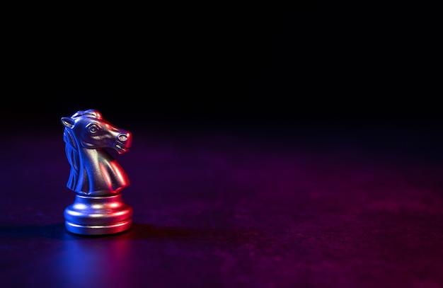 Goldenes schachpferd, das allein auf dem schachbrett mit roten und blauen lichtern auf dunklem hintergrund steht