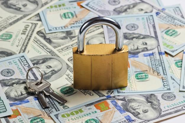 Goldenes schloss mit schlüssel auf hintergrund von dollarnoten