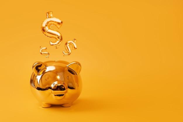 Goldenes sparschwein auf gelbem hintergrund mit gold-usd-zeichenballons. goldenes währungssymbol aus aufblasbarem folienballon. investment- und bankkonzept. geld sparen, sparbüchse, finanzen, investitionen.