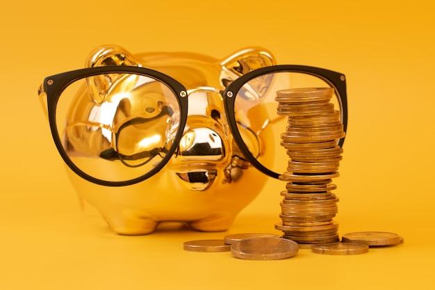 Goldenes sparschwein, das brille mit geldturm trägt