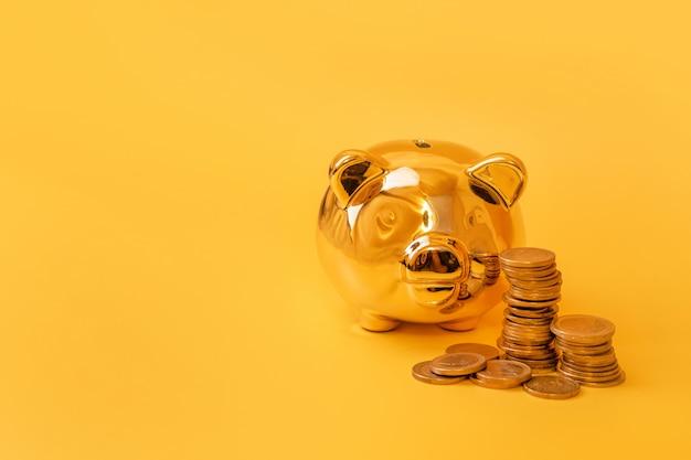 Goldenes sparschwein mit geldtürmen auf gelbem hintergrund