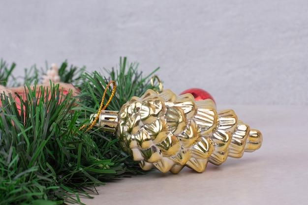 Goldenes spielzeug des tannenzapfens auf grünem lametta auf weißer oberfläche
