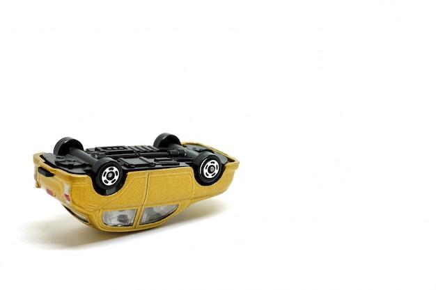 Goldenes spielzeugauto auto warf auf einem weißen hintergrund, modell des autounfalls um
