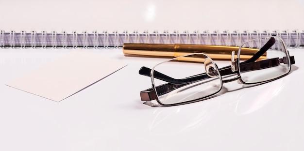 Goldenes stiftnotizbuch und brille in komposition in schwarz-weiß und goldenem geschäftskonzept
