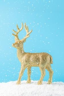 Goldenes weihnachtsrentier unter schneefall auf blau
