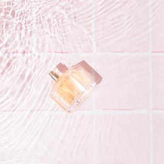 Golder parfüm in wasser mit kleinen wellen auf pastellrosa hintergrund mit fliesen. luxuriöse weibliche schönheitsprodukte. minimaler stil.