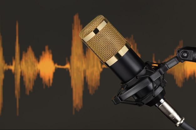 Goldfarbenes kondensatormikrofon über computermonitorhintergrund mit wellenform. tonaufzeichnungskonzept