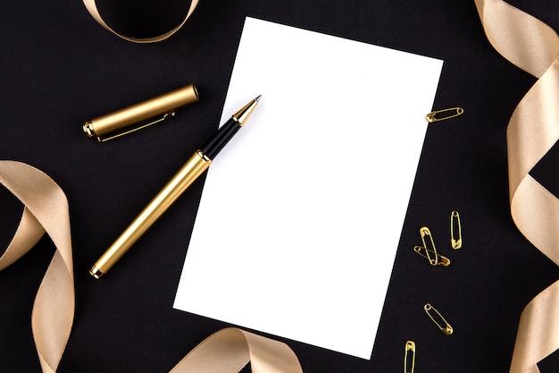 Goldfeder, farbband, papierklammern und briefpapier auf einem schwarzen hintergrund mit einem weißen blatt papier mit exemplarplatz