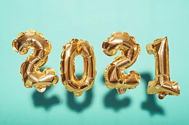 Goldfolienballons mit den nummern 2021 auf blau