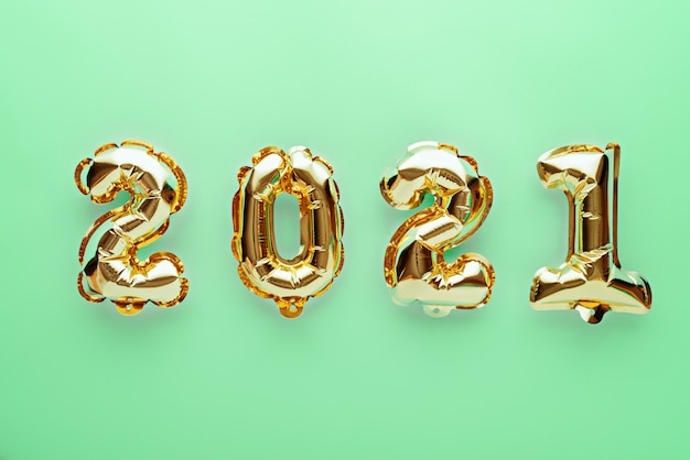 Goldfolienballons mit den nummern 2021 auf grün