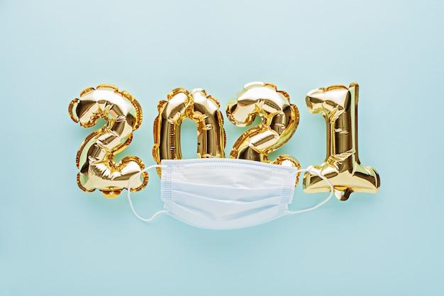 Goldfolienballons nr. 2021 mit medizinischer maske auf blau