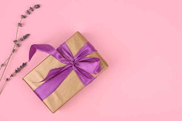 Goldgeschenkbox mit violettem band und lavendel. rosa hintergrund mit kopienraum