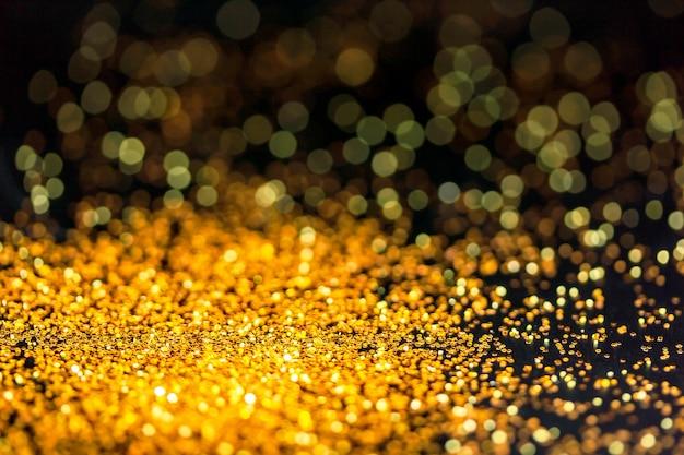 Goldglitterpulver, das auf schwarzem hintergrund funkelt.